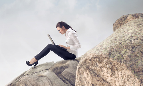 Woman with laptop on mountain. Image courtesy of Shutterstock