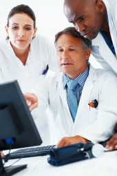 Doctors around computer, courtesy of Shutterstock