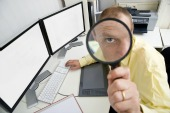 Man with magnifying glass, courtesy of Shutterstock