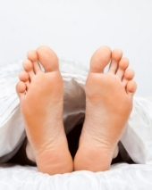 Bare feet in bed. Image from Shutterstock