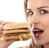 Woman eating burger, courtesy of Shutterstock