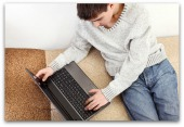 Teenager with computer. Image courtesy of Shutterstock