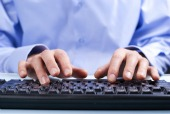 Hands on computer. Image courtesy of Shutterstock