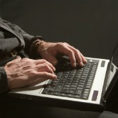 Man on computer. Image courtesy of Shutterstock