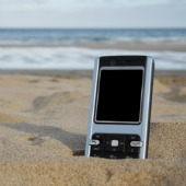 Phone in sand. Image courtesy of Shutterstock.