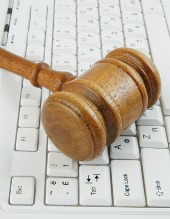 Gavel on keyboard, image courtesy of Shutterstock